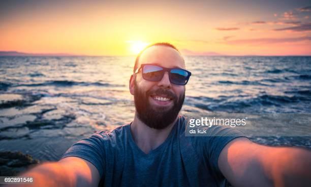 Happy tourist making selfie standing near sea