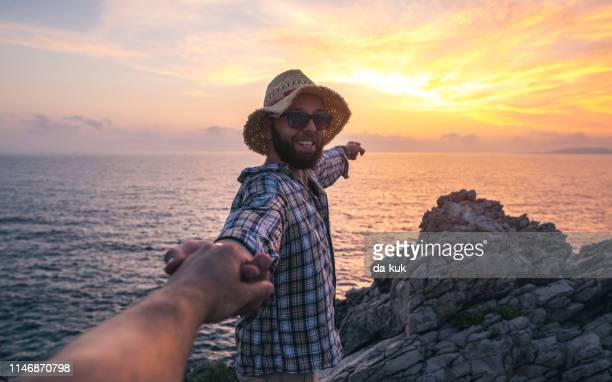 happy tourist taking selfie standing on rocks - following stock pictures, royalty-free photos & images