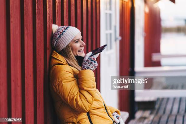 happy tourist using smartphone at hamnoy, lofoten, norway - winter coat stock pictures, royalty-free photos & images