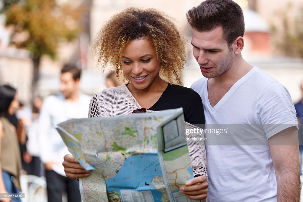 Happy tourists couple holding map : Stock Photo
