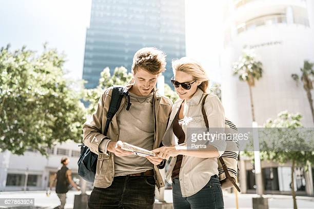 Happy tourists reading map while standing in city