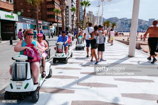 Happy tourists riding mobility scooters on Levante beach promenade
