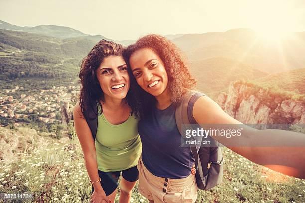 Happy tourists taking selfie on the mountain peak