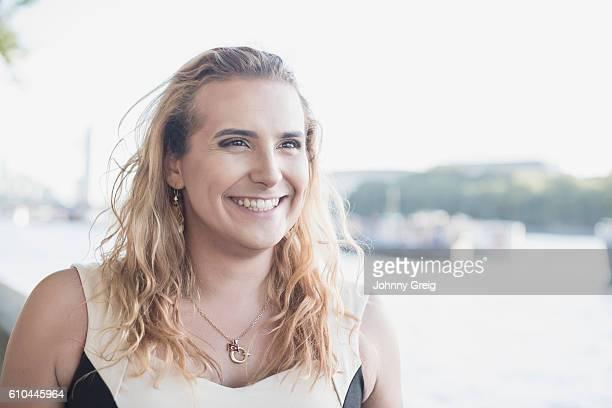 Happy transgender female smiling, looking away
