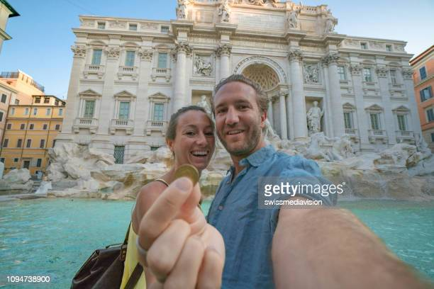 happy travel couple trowing coin at trevi fountain, rome, italy for good luck. young couple smiling traveling together on romantic travel vacation holiday in europe. caucasian couple - trevi fountain stock photos and pictures