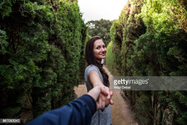 Happy traveler couple enjoying visiting gardens inside maze in the Barcelona city during travel vacations with boyfriend holding hand taken picture from personal perspective. Follow me.
