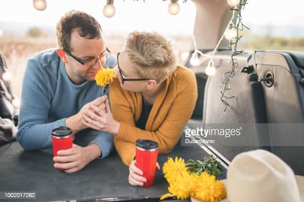Happy traveler couple sitting in car open trunk