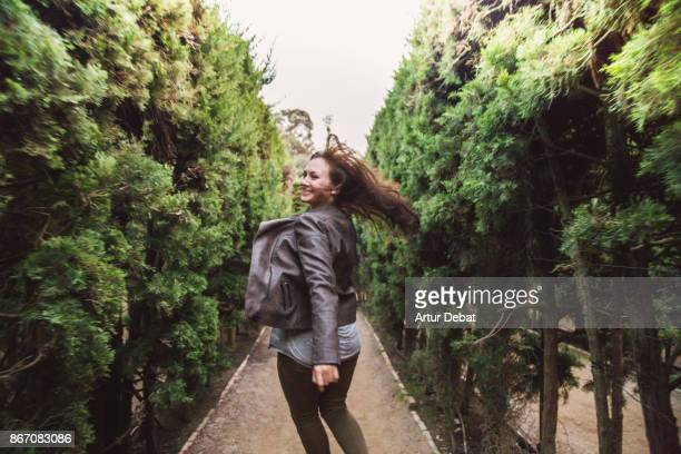 Happy traveler girl enjoying visiting gardens with maze in the Barcelona city during travel vacations in autumn, running and laughing looking at camera with hair in motion.