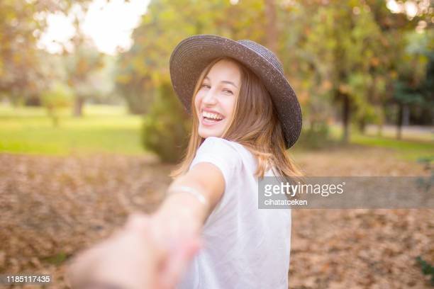 happy traveler girl holding hand of her boyfriend - social media followers stock pictures, royalty-free photos & images
