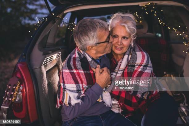 Happy traveler senior couple sitting in car open trunk