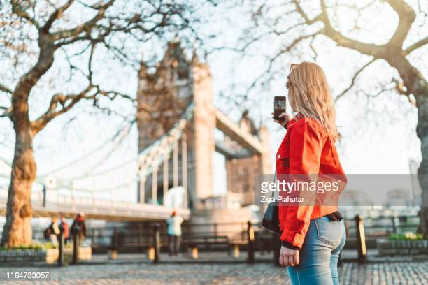 happy traveler sightseeing london, taking a photo of tower bridge - tourist stock pictures, royalty-free photos & images