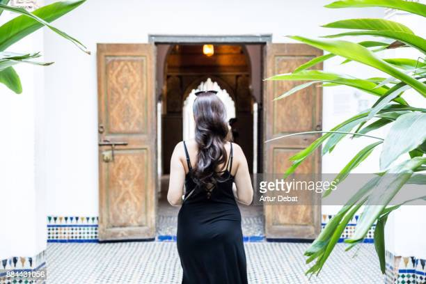 Happy traveler woman visiting beautiful white palace in Marrakech city with nice open patio and fountain during travel vacations in Morocco.