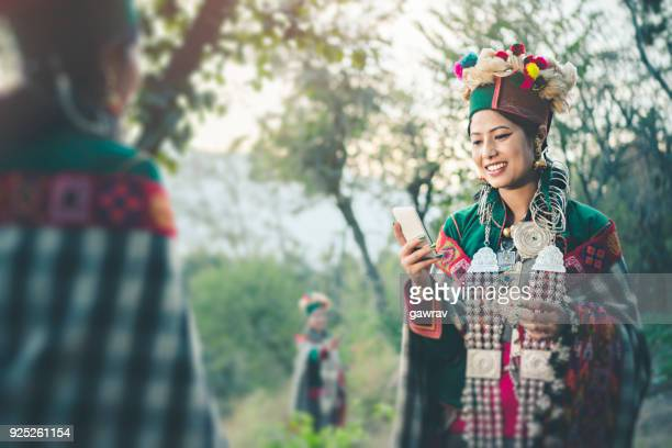 Happy tribal young woman of Kinnaur using smart phone.