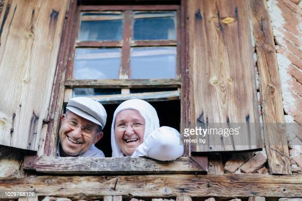 gelukkig turkse echtpaar op zoek door raam - heteroseksueel koppel stockfoto's en -beelden