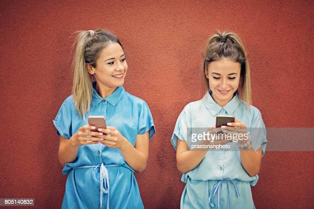 Happy twin sisters are texting