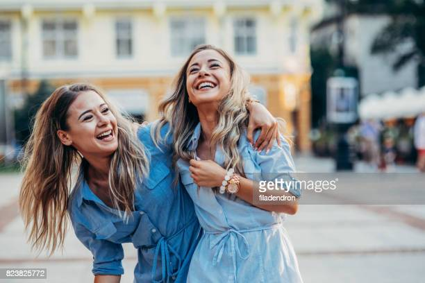 happy twins in the city - arm around stock pictures, royalty-free photos & images