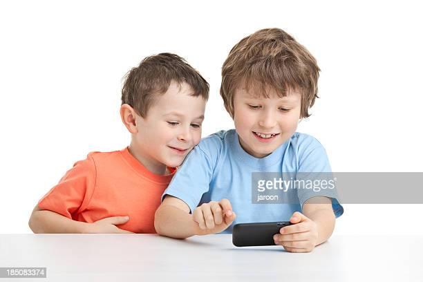 Dos hermanos felices jugando con el teléfono inteligente