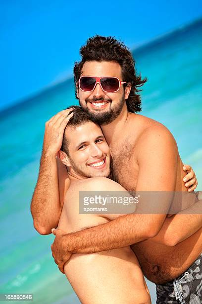 happy two friends hugging on a tropical turquoise beach - human relationship stock pictures, royalty-free photos & images