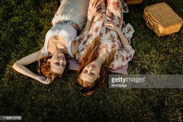 glückliche zwei frauen liegen an einem sonnigen tag im gras - lying down stock-fotos und bilder