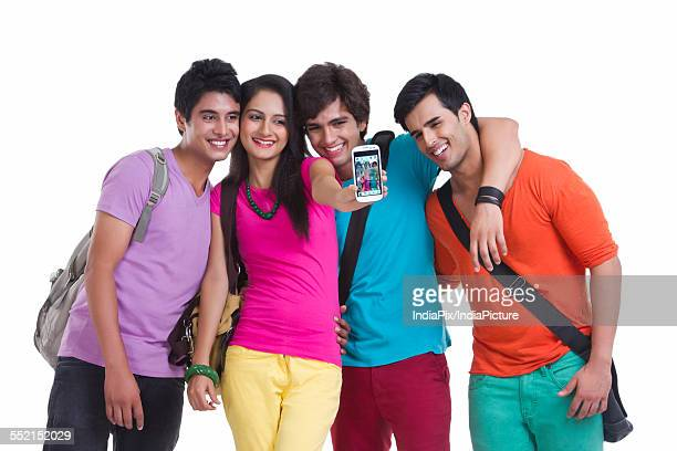 Happy university friends taking picture of themselves over white background