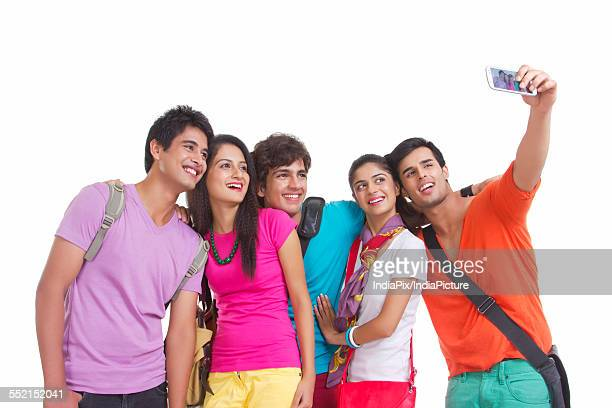 Happy university friends taking self-portrait with smart phone on white background