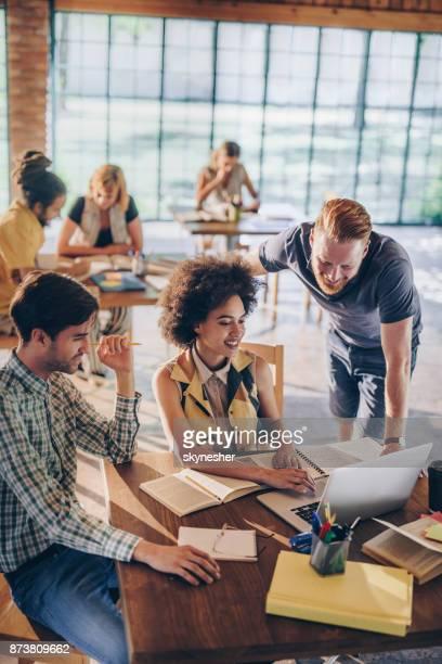 glad universitetsstuderande samarbeta medan e-learning i biblioteket. - group e bildbanksfoton och bilder