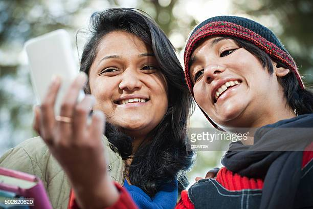 Happy university students sharing smart phone in outdoor.