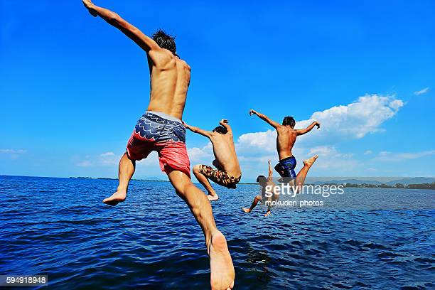 Happy Vacation Young Japanese boys  jumping into Lake