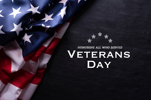 Happy Veterans Day. American flags with the text thank you veterans against a blackboard background. November 11. 1182367020