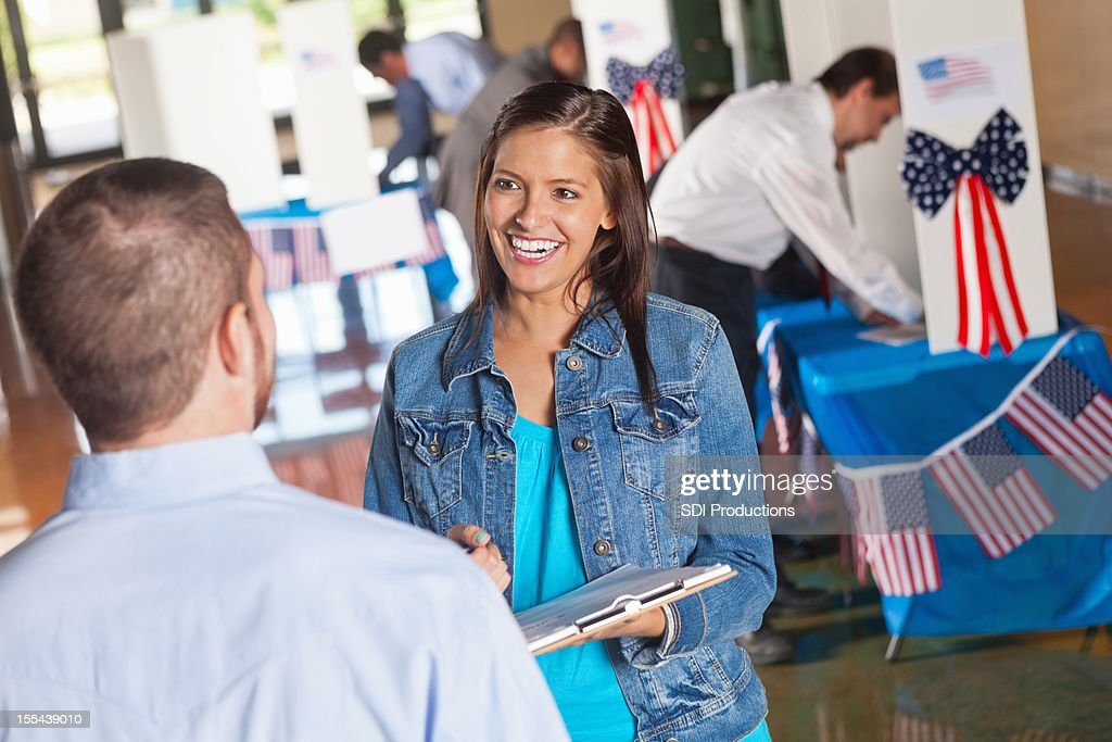 Happy volunteer asking exit poll questions at election voting center : Stock Photo
