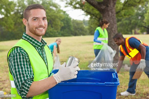 Happy volunteer picking up trash/ recycling with community service group