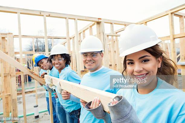 Happy volunteer team build home for charity