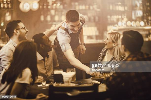 happy waiter having fun with group of people in a bar. - wait staff stock pictures, royalty-free photos & images