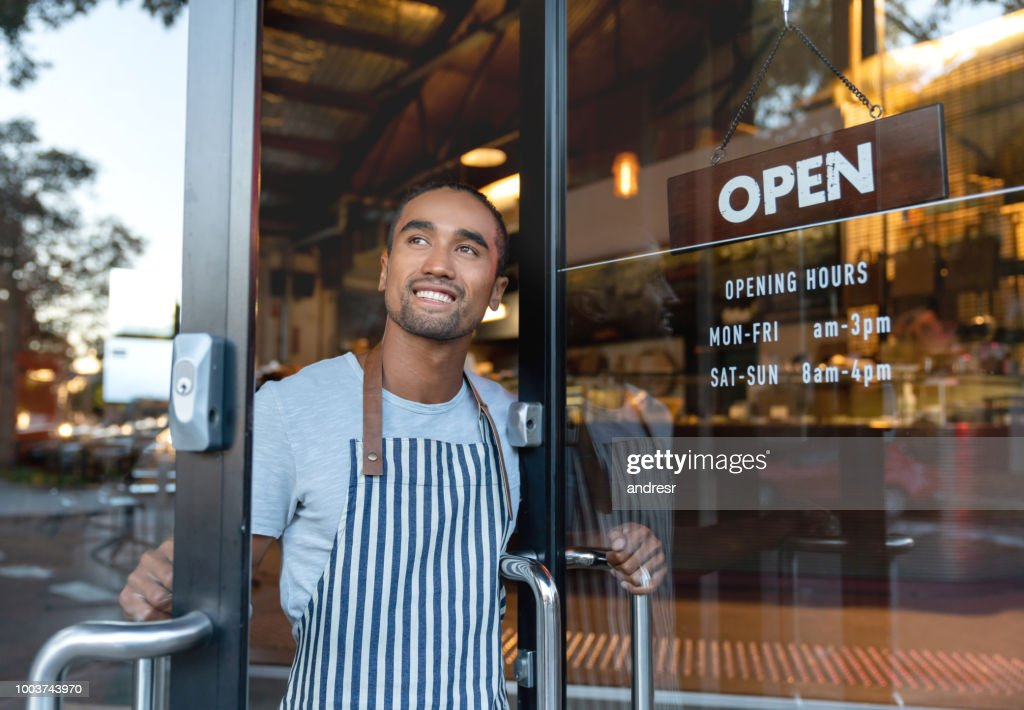 Happy waiter opening on the doors at a cafe : Stock Photo