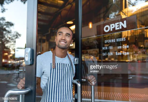 happy waiter opening on the doors at a cafe - porta imagens e fotografias de stock