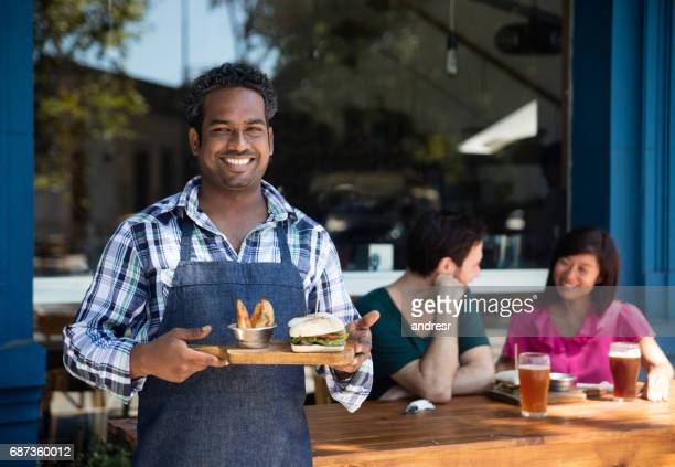 happy waiter serving food at a restaurant - catering building stock pictures, royalty-free photos & images