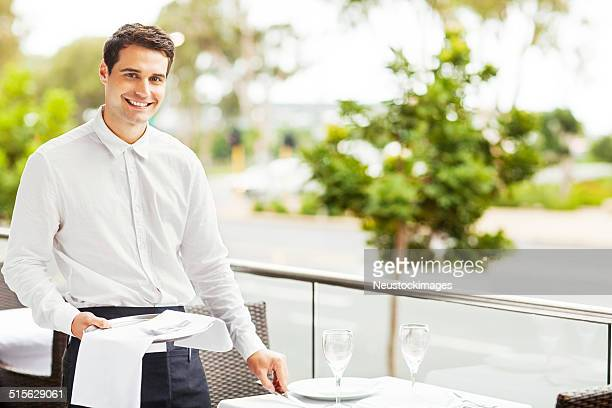Happy Waiter Setting The Table In Restaurant