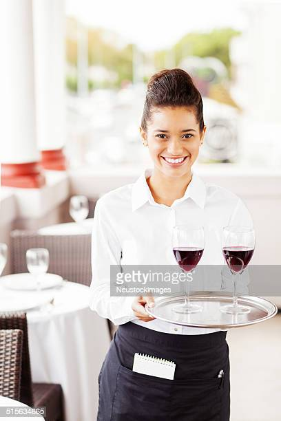 Happy Waitress Carrying Tray With Wine Glasses In Restaurant