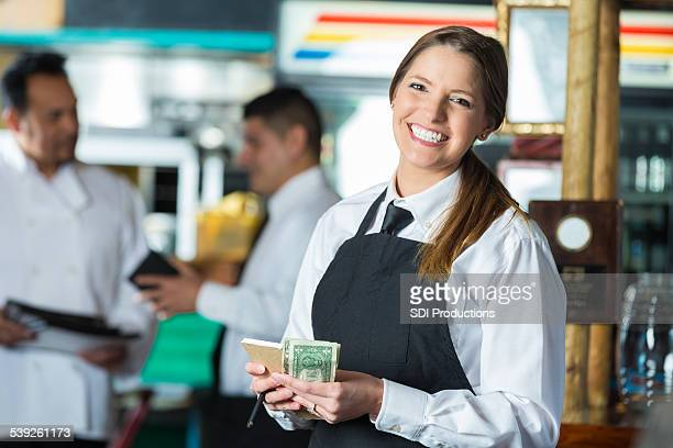 Happy waitress in Tex-Mex restaurant counting cash tips