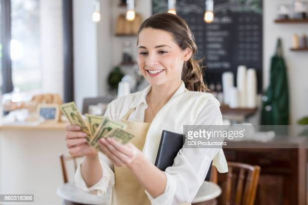 Happy waitress is pleased after receiving a large tip
