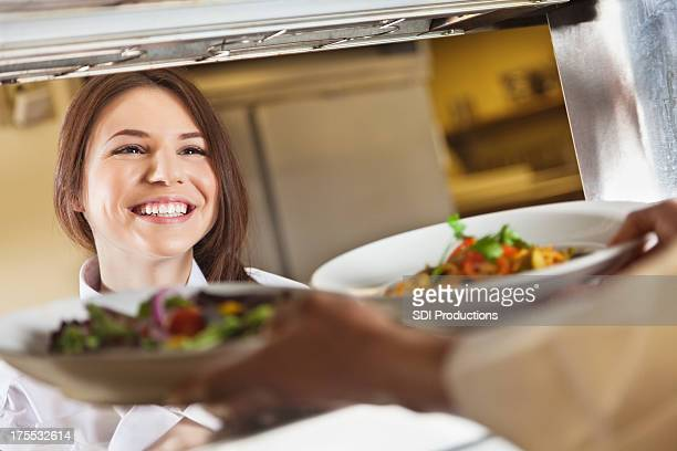 Happy waitress receiving food from chef in commercial restaurant kitchen