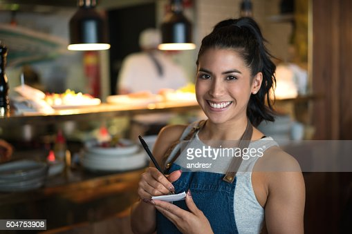 Happy waitress working at a coffee shop : Stock Photo