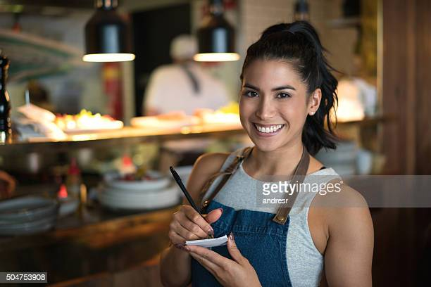 Happy waitress working at a coffee shop