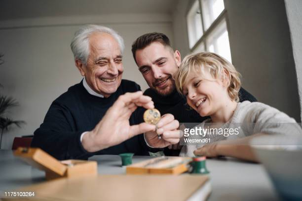 happy watchmaker showing clockwork to young man and boy - watch timepiece stock pictures, royalty-free photos & images