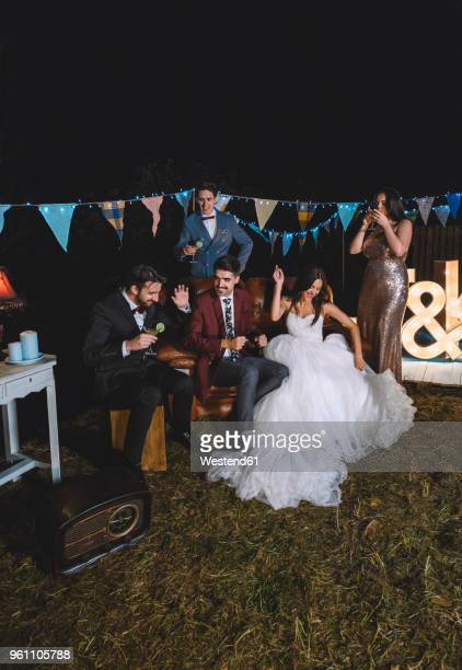 Happy wedding couple having fun sitting on sofa with their friends on a night field party