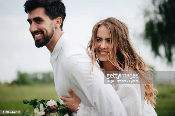 Happy Wedding Couple Standing On Field Against Sky