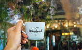 Happy weekend text on mug with cafe view
