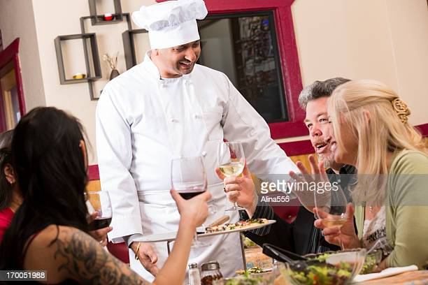 Happy welcoming chef with customers in a restaurant