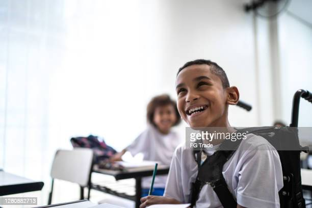 happy wheelchair student studying in the classroom - wheelchair stock pictures, royalty-free photos & images