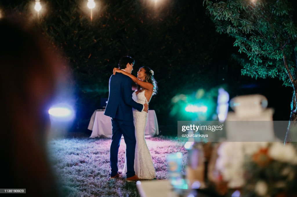 Happy wife and groom dancing at night outdoors wedding reception : Stock Photo